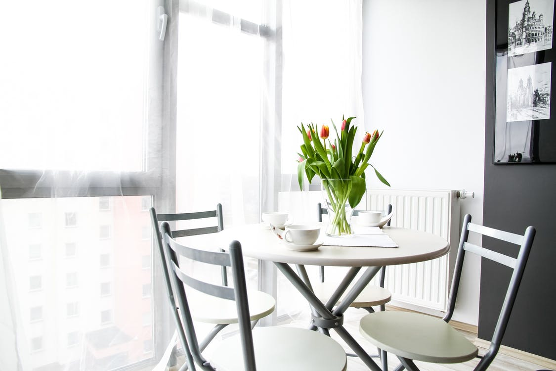 Empty Chairs Beside Table With Tulip Flowers